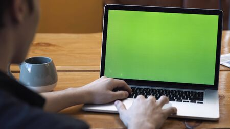 View from the back of man in black shirt sitting at the table and typing on laptop with green chroma key screen. Stock footage. Laptop new technology concept, chroma key green screen