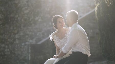 Beautiful newlyweds sitting in sunlight. Action. Beautiful bride and groom sit and look at each other illuminated by bright sunlight. Sincere and tender love of young people