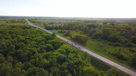 Top view of track with traffic on background of green trees. Shot. Landscape highway with passing cars on background of green trees and horizon with sky. Summer road trips