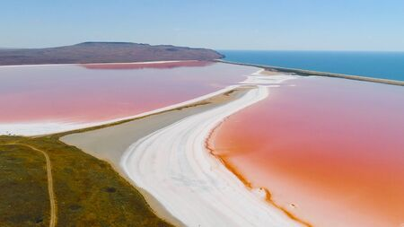 Top view of pink lakes on blue sea background. Shot. Bright colorful lakes of pink and orange colors are separated by white coast from blue sea. Natural phenomenon of pink lakes 스톡 콘텐츠