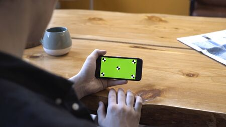 View from the shoulder of young man in black shirt sitting at wooden table and looking at phone chroma key green screen at home. Stock footage. Smartphone new technology concept