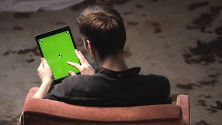View from the back of young man in black shirt sitting in the chair and tapping on green mock-up screen of digital tablet computer with tracking marks. Stock footage. Chroma key screen