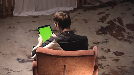 View from the back of young man with brown hair holding black tablet computer with green screen while sitting on the sofa at home. Stock footage. Chroma key