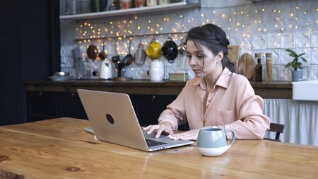 Concentrated young woman sitting in the kitchen at wooden table and typing on her personal silver laptop with the cup of tea or coffe. Stock footage. Modern decorated home interior on the background Imagens