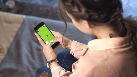Pretty woman with brown hair sitting at home in pink shirt and sliding on her smartphone at the chroma key green screen. Stock footage. Smartphone new technology concept