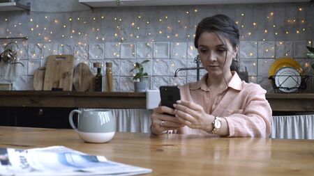 Beautiful young woman with brown hair in pink shirt sitting in the kitchen at wooden table and using smartphone. Stock footage. Modern decorated home interior on the background