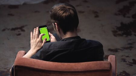 Top view of young man with brown hair sitting in chair and tapping on iPhone green screen in dark room. Stock footage. Chroma key Imagens