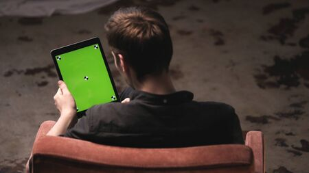 Man with brown hair in black shirt sliding on green mock-up screen of digital tablet computer with tracking marks. Stock footage. Chroma key screen for placement of your own content.
