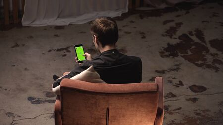 Attractive young man with brown hair sitting in comfortable chair with white pillow and sliding on iPhone green screen in dark room. Stock footage. Chroma key