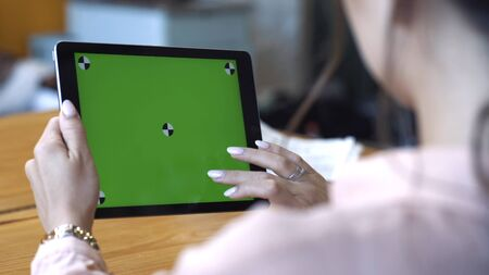 View from the shoulder of young woman in pink shirt sitting at the table and sliding on her tablet at the chroma key green screen. Stock footage. Chroma key screen for placement of your own content.
