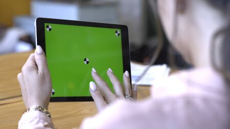Close-up of young woman with brown hair sitting at the table and sliding on her tablet at the chroma key green screen. Stock footage. Chroma key screen for placement of your own content. Imagens