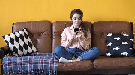 View of young pretty woman in pink shirt and jeans sitting on the brown couch with pillows and typing on her smartphone. Stock footage. Woman relaxing at home
