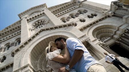 Kissing couple in background of Cathedral. Action. Lovely young couple kissing at European beautiful Cathedral. Newlyweds on honeymoon in Europe