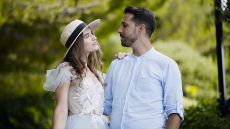 Lovely young couple admiring each other. Action. Newlyweds stand in embrace against each other and throw gentle glances. Couple stand in embrace against green park on honeymoon Standard-Bild - 129373892
