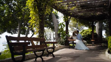 Couple sitting on bench in beautiful gazebo. Action. Beautiful couple sitting in gazebo in honeymoon. Husband kisses his precious wife on cheek. Sweet and romantic couple