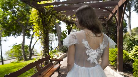 Young beautiful bride stand in white dress in garden. Action. Rear view of young bride in delicate white dress standing in green garden under gazebo