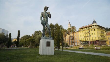 Statue of David in park. Action. Beautiful manly statue of David stands in park on background of sky. Nude statue of David is made of dark stone and stands on pedestal in park