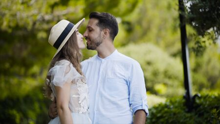 Lovely young couple admiring each other. Action. Newlyweds stand in embrace against each other and throw gentle glances. Couple stand in embrace against green park on honeymoon Standard-Bild - 129373691