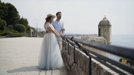 Beautiful young couple on honeymoon. Action. Newlyweds on stone observation deck admiring seascape. Beautiful newlyweds in embrace looking at landscape