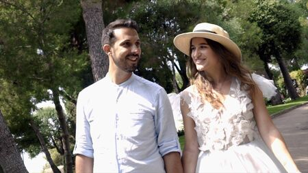 Newlyweds are smiling and holding hands in park. Action. Beautiful young couple beaming with happiness on honeymoon. Young wife in hat smiles at husband