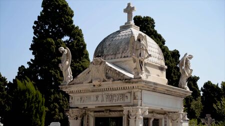 Beautiful crypt in cemetery. Action. Burial structure with dome in cemetery means crypt. European cemetery with white architectural buildings of crypts, statues and plates