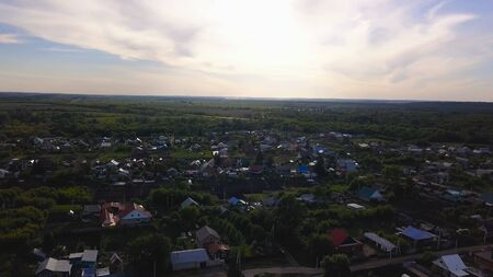 Top view of panorama of village on background of green forest. Clip. Cottage town is great place for quiet life near nature without hustle and bustle of city Stok Fotoğraf