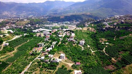 Top view of green city located in mountains. Clip. Town is surrounded by green vegetation and trees in mountains. Resort town is located on uneven mountainous terrain in summer.