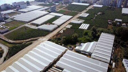 Top view on city of plantation greenhouses. Clip. Area of city with agriculture on cultivation of food vegetation near residential areas. Urban agriculture on coast in summer. Zdjęcie Seryjne