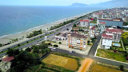 Top view of white towers of mosque. Clip. Beautiful high towers of mosque on background of coastal city with blue sea. Resort town with white mosque. Muslim religion.