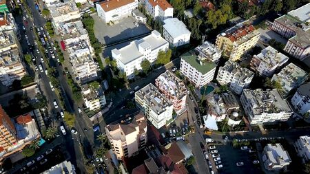 Top view of roofs and streets of city in summer. Clip. Beautiful southern city with orange roofs, high-rise buildings and green vegetation. Resort town for summer holidays. 版權商用圖片