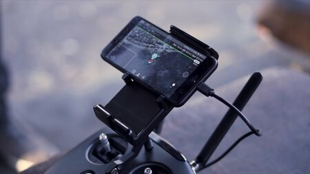 Close up for smartphone with working application Google Maps with destination point, navigation concept. Clip. Smartphone holder with a phone and usb cable. Stock Photo