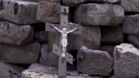 Close up for the wooden cross with crucified Jesus on stone bricks background, Bible and religion concept. Footage. Religious attribute of the church, Christian symbolism.