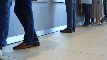 View of legs of customers standing n the modern office, getting served in the bank. Media. People are queuing for service in the department of a bank.