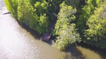Peaceful river and forested shore, shot by drone. Clip. Aerial for the natural landscape with a river, wooden pier and many green trees along the coast in a sunny summer day. Stock Photo