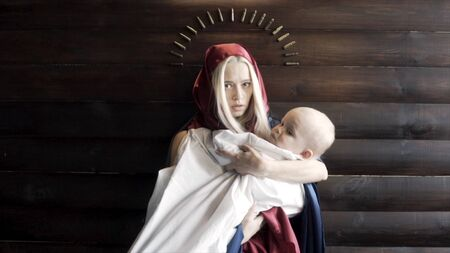 Woman with the covered head, mother with a baby in her arms standing against wooden wall with an arc of bullets, religion and war concept. Footage. The image of the virgin Mary and a Jesus.
