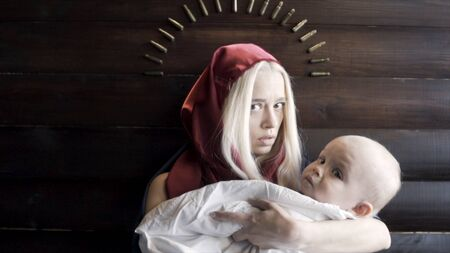 Close up of a scared young woman weaing red hood holding a baby in white sheet on wooden wall background. Footage. An image of Virgin Mary and Jesus, religion concept.