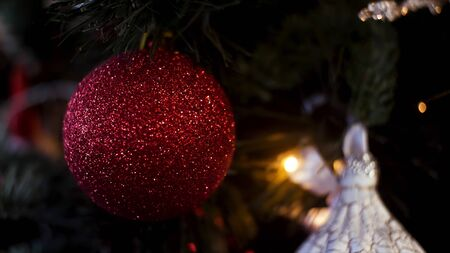 Decorated Christmas tree on blurred, sparkling and fairy background, merry christmas and happy new year concept. Frame. Close up for red shining ball and illuminated garland with flashlights.