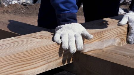 Close up for worker hands in protective glass touching wooden beams bonded to each other, house building concept. Clip. Professional carpentry work. Stock Photo