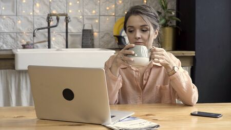 Woman working from home using laptop In the kitchen. Stock footage. Cute brunette woman drinking tea from grey and beige mug, working on laptop, freelance concept.