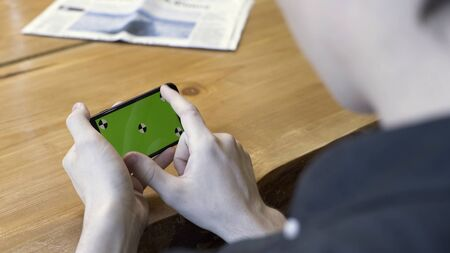 Smartphone horizontal orientation with a green screen: shot over the shoulder of a young man. Stock Footage. Man sitting at the table, tapping, scrolling, and zooming on the chromakey of the phone.