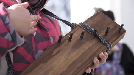 Close up for hands of a little child trying too play the traditional stringed instrument. Clip. A girl playing unusual music instrument outside.