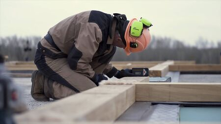 Side view of a man worker in uniform and protective helmet setting laser level tool at the construction site. Clip. Male builder using laser spirit level to make the wooden house base.