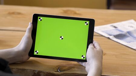 Young guy holding the tablet with touching green screen with tracking marks, motionless. Stock footage. Modern device or  big chromakey monitor on wooden table background. Zdjęcie Seryjne