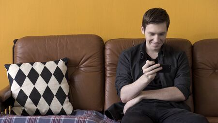 Technology concept, man watching funny video on smartphone and sitting on a cozy brown leather couch with black and white pillow. Stock footage. Young man using modern device.