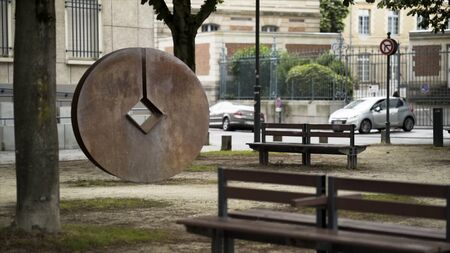Modern city park with benches and metal round statue with a diamond-shaped hole in the middle of it. Stock footage. A public place with trees near the road.