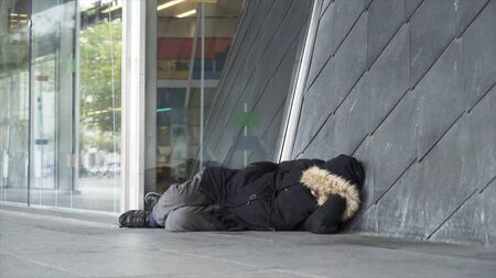 Homeless man in warm clothes sleeping outdoors near the entrance of the building, poverty concept. Stock footage. Poor unemployed male tramp lying near the concrete wall.
