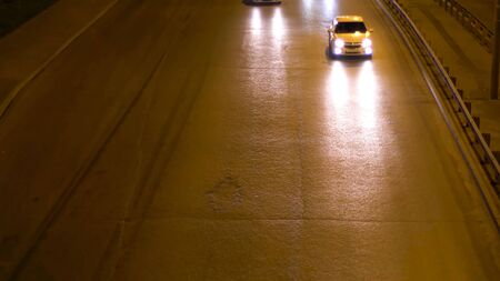 Aerial view of the city road at night illuminated by street lamps with moving cars, night traffic. Stock footage. Top view of the vehicles driving on the dark road under the street lights. 版權商用圖片