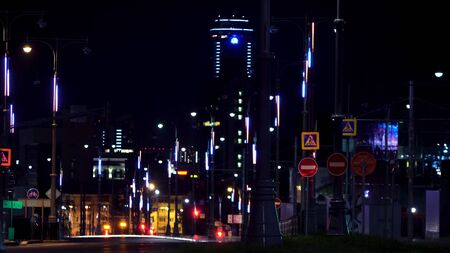 Night landscape of a modern city full of neon lights with cars moving on the road. Stock footage. Night road lit by many neon street lamps and driving cars.