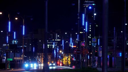 Street of a night city with moving cars along street lamps with a skyscraper on the background, Ekaterinburg, Russia. Stock footage. Cars driving on the night road, time lapse.
