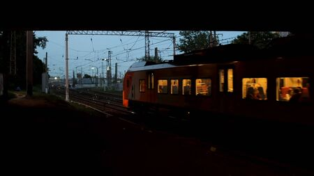 The train passing under the bridge in the summer evening, transportation concept. Stock footage. Train wagons with people inside running on the rails.